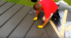 man installing metal sheet panels on roof
