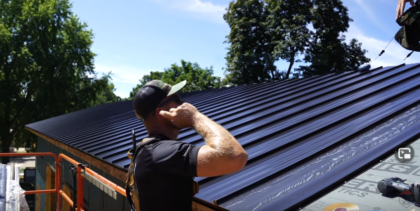 Man in front of a standing seam metal roof
